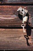 Mit Schwimmkorken gesicherter Bootsschlüssel an Nagel vor rustikaler Holzbalkenwand gehängt