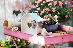 Birdhouse hand-crafted from white and sky blue felt on rusty, pink tray table