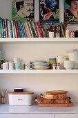 Küchenunterschrank mit Holzbrettern, darüber Wandborde mit Büchern und Geschirr unter Filmplakaten