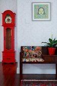 Telefonbank mit Musterkissen, gerahmtes Bild und rot lackierte, antike Standuhr in tapezierter Diele