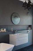 Zierspiegel und moderner Waschtisch an anthrazitfarbener Wand mit langgestreckter Nische