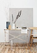 Painted, dried branches and plant stems in designer vases made from natural materials on vintage folding table