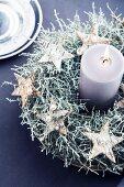 Mit Silberdraht und aufgefädelten Perlen umwickelte Sterne aus Birkenrinde als Dekoration auf einem Kranz aus der silbrig-grünen Stacheldrahtpflanze