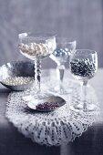 Bastelperlen in Silberschälchen und Weingläsern auf einem Spitzendeckchen