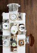 Top view of artistically set table - place settings with various motifs on plates and white table cloth