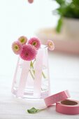 Glass jar with decorative masking tapes, pink daisies inside