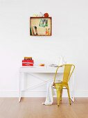 Books, pens and ornaments on and in wooden crate with patterned back panel mounted on wall; small desk and yellow, retro metal chair