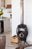 Mit Holz befüllter Keramikofen auf Edelstahlplatte im offenen Wohnraum