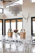 Metall Esstisch mit Ghoststühlen in hohem Wohnraum mit Glasfronten zur Terrasse und Fensterband