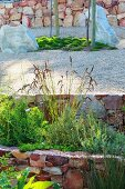 Terrassengarten mit Natursteinmauern und verschiedene Gräser
