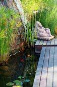 Steinfigur am Ende eines Holzsteges über Teich mit Wasserpflanzen