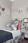 Hearts and framed mirrors above bed with frame upholstered in Toile de Jouy fabric