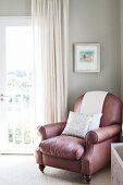 Leather armchair in corner of room against pale grey wall next to window with floor-length curtain