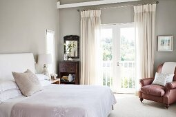 Double bed with headboard and white bed linen in front of balcony door and leather armchair