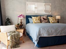 Double bed with frame and headboard upholstered in blue below window with closed interior shutters and rattan armchair