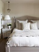Elegant bed linen on pale grey antique bed with headboard next to bedside table and table lamp in rustic ambiance
