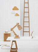 Wooden objets d'art in white room - table lamp made from wooden components on white table top with trestles in front of various objets and vintage ladder leaning on wall