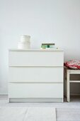 Set of storage boxes on simple, white chest of drawers against wall