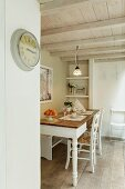 Dining area in rustic ambiance with wooden ceiling and simple, vintage clock