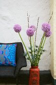 Zwiebelblüten in einer Vase neben Sessel mit Dekokissen