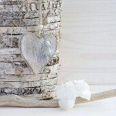 Holzherz hängt an einem Stamm aus Birkenscheiben