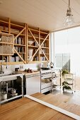 Table made from wooden boards of different lengths in modern kitchen opposite wooden shelves above stainless steel kitchen counter