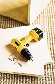 Yellow cordless drill-driver lying on cut plywood panel