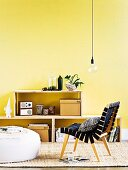 DIY, plywood shelving against yellow wall behind retro chair and pouffe on sisal rug