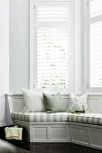 Comfortable, elegant, grey wooden window seat with striped seat cushions in white bay window with louver blinds - perfect for reading and relaxing