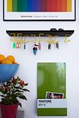 Bright colours in hallway - original key rack, magnet board with magazine rack and framed poster of colour field artwork