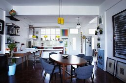 Oval dining table and vintage, Scandinavian furniture in open-plan interior with desk and kitchen in background