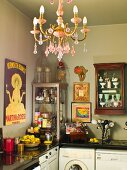 Corner of kitchen with antique crockery in display cabinets above worksurface; chandelier with pink crystal ornaments in foreground