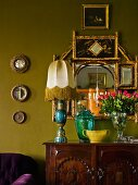 Table lamps, various glass vessels and vase of roses on chest of drawers in front of arrangement of mirrors on green-painted wall