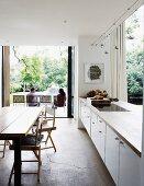 Offene Küche mit weisser Küchenzeile als Raumteiler und Terrassenzugang