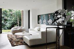 Weisses Ledersofa übereck mit rundem Couchtisch und Sitzsack vor offener Terrassenfront