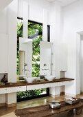 Zwischen Wände eingespannter Waschtisch mit Aufsatzbecken und Spiegel vor Fenster, vorne rustikale Holzbank