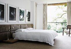 Doppelbett vor Wand mit halbhoch gepolsterten Lederpaneelen unter Fotogalerie, Blick in Garten durch raumhohes Fenster