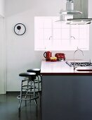 Retro bar stools at modern island counter with sink and gas hob below extractor hood