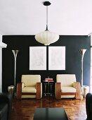 Hängeleuchte mit Stoffschirm in modernem Wohnzimmer mit mächtigen Sesseln vor schwarzer Wand zwischen trichterförmigen Designer-Stehleuchten