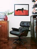Lounge chair with black leather cover in corner in front of framed picture of cat
