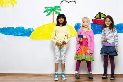 Three girls with paintbrushes standing in front of mural on wall