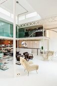 Spacious loft apartment with partition shelving, group of armchairs with arc lamp and modern kitchen below sleeping area on gallery; natural light falling through lantern skylight
