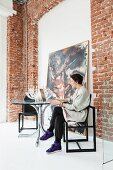 Woman sitting on designer chair at round glass table next to brick wall of loft interior with painting leaning on wall