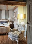 Rustic bedroom with Rococo armchairs, standard lamp and antique, French bed
