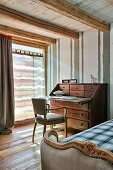 Partially visible bed with antique frame and chair at bureau in rustic bedroom