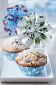 Colourful paper flowers attached to small wooden forks decorating muffins