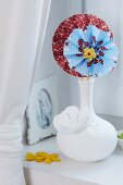 Colourful paper flowers in white china vase