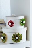 Colourful paper flowers decorating set of white storage boxes