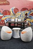 Garden table and chairs and wicker side table with two shell chairs in front of house wall painted with graffiti