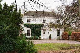 View of traditional, English country house across autumnal garden
